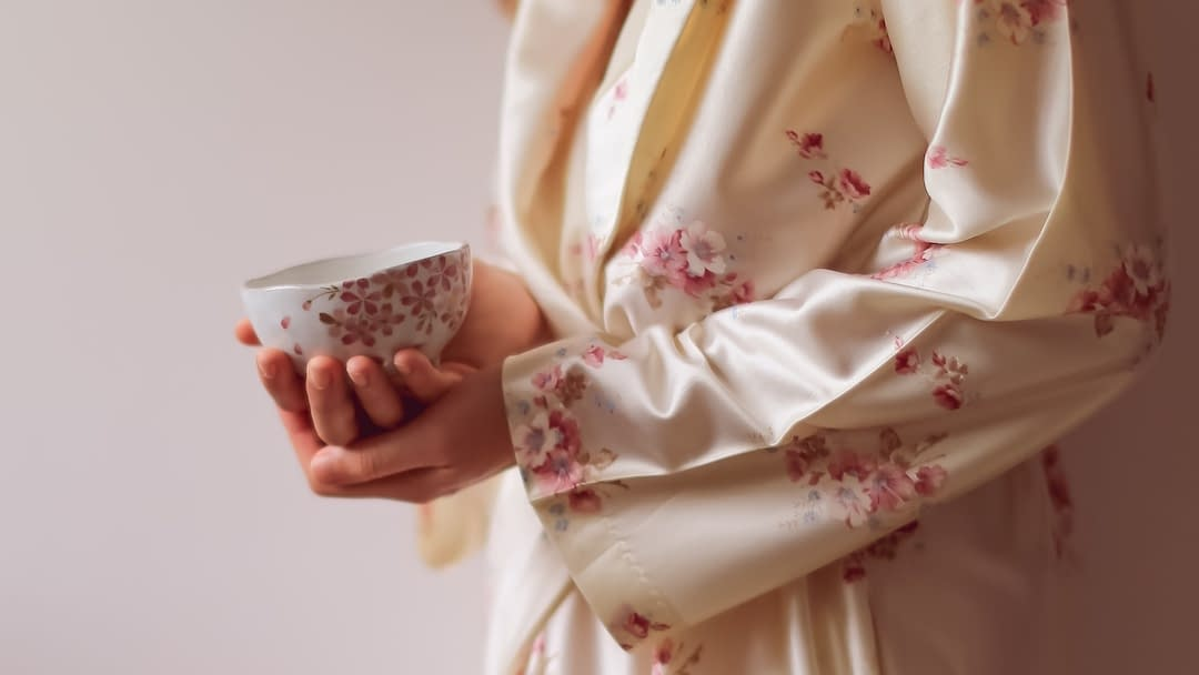 woman in robe holding cup