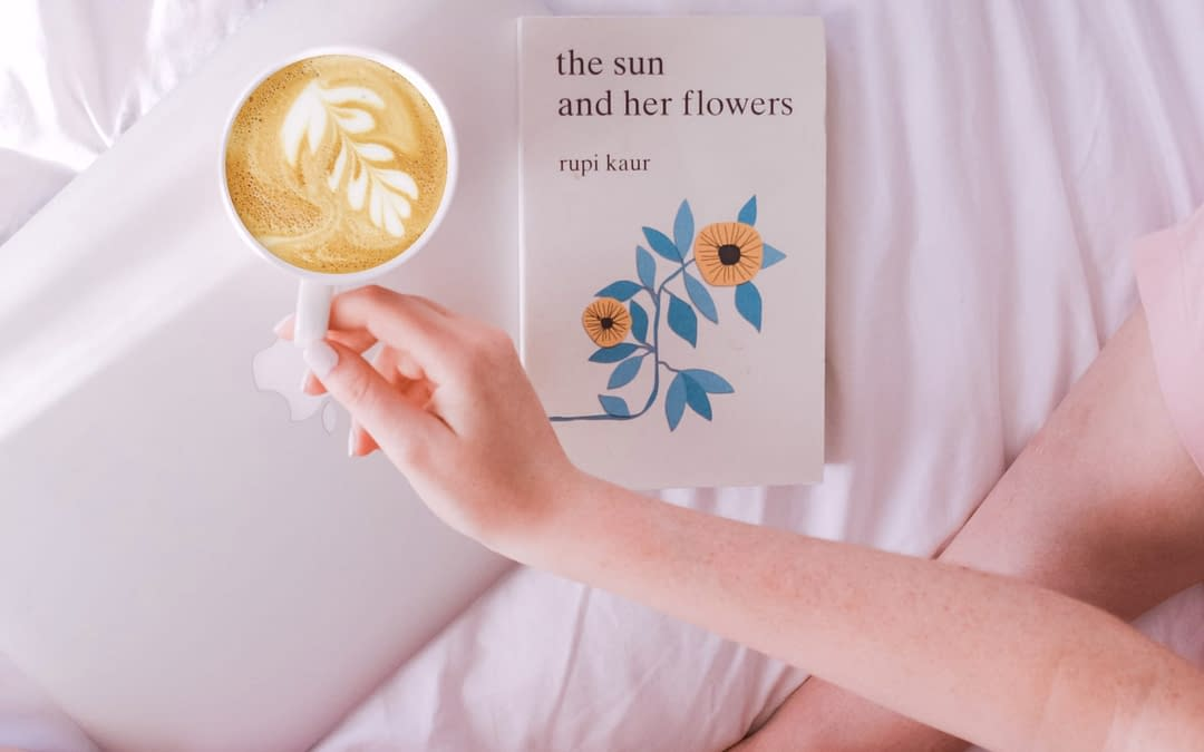 girl on bed with book and coffee